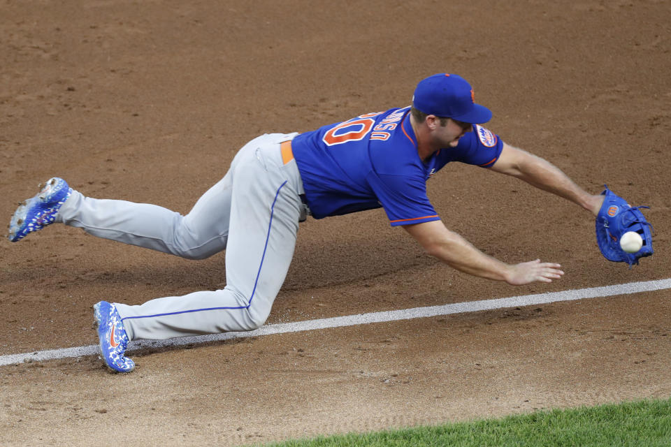 New York Mets first baseman Pete Alonso cannot reach the throw to first on an error by Mets second baseman Robinson Cano which allowed New York Yankees Gleyber Torres to reach base in the third inning of an exhibition baseball game, Sunday, July 19, 2020, at Yankee Stadium in New York. (AP Photo/Kathy Willens)