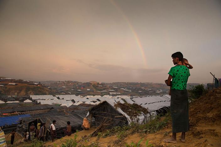 <p>A Rohingya man holds his child as he looks at a rainbow on a hill overlooking the Kutupalong refugee camp on September 22, 2017. (Photograph by Paula Bronstein/UNHCR) </p>