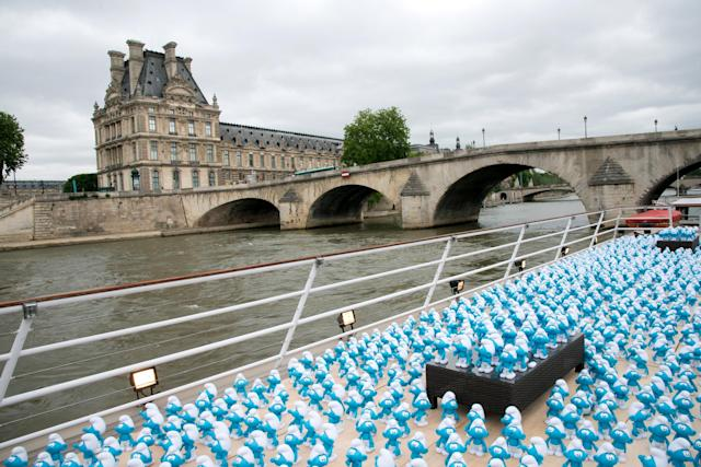 PARIS, FRANCE - JUNE 22: 3000 smurf figurines pass The Louvre as they travel down the River Seine to mark Global Smurfs Day on June 22, 2013 in Paris, France. (Photo by Dominique Charriau/Getty Images for Sony Pictures Entertainment)