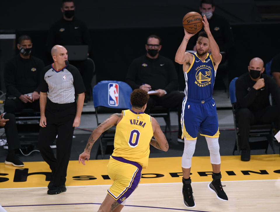 Stephen Curry #30 of the Golden State Warriors shoots a three pointer in front of Kyle Kuzma #0 of the Los Angeles Lakers during a 115-113 Warriors win on Martin Luther King Jr. Day at Staples Center on January 18, 2021 in Los Angeles, California.