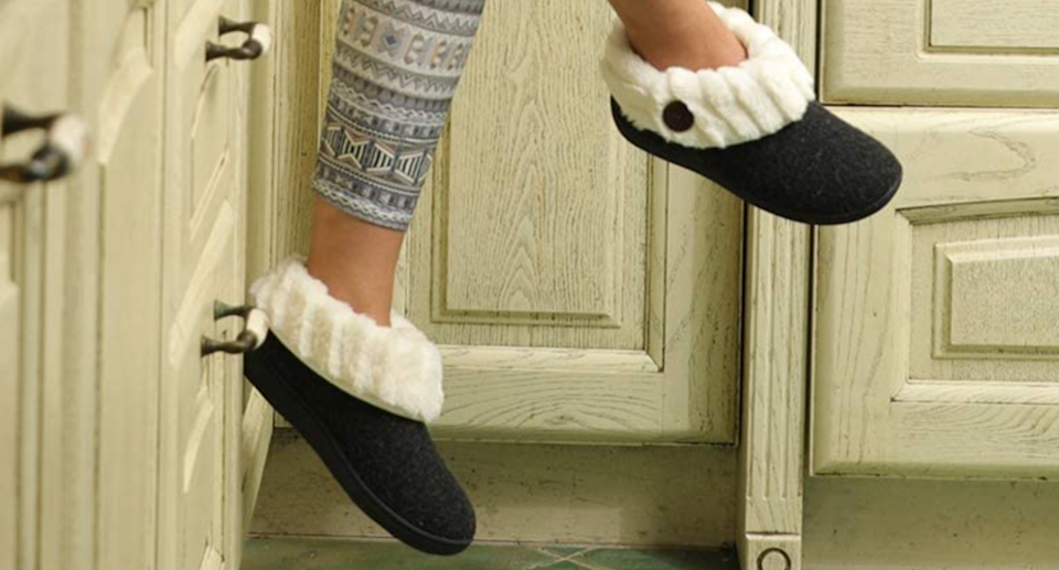 woman feet dangling wear black slippers with white faux fur sitting on kitchen cabinet