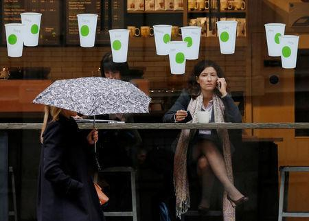 FILE PHOTO: A woman carrying an umbrella walks in the rain past a Starbucks coffee shop in London, October 8, 2012. REUTERS/Luke Macgregor/File Photo