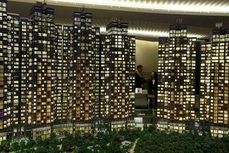 Attendants chat behind the model of a residential development in Hong Kong March 20, 2015. REUTERS/Bobby Yip