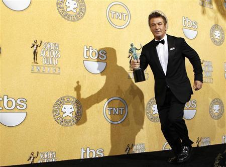 Actor Alec Baldwin runs backstage with his award at the 18th annual Screen Actors Guild Awards in Los Angeles