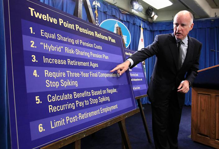 """In this Oct. 27, 2011, file photo, Gov. Jerry Brown gestures to a chart showing some of his proposals to rollback public employee pension benefits during a news conference at the Capitol in Sacramento, Calif. California's decades-old protections for public employees' retirement benefits are not enough to bar state lawmakers from enacting reforms designed to prevent abuses such as """"pension spiking,"""" the state Supreme Court unanimously ruled Thursday, July 30, 2020."""