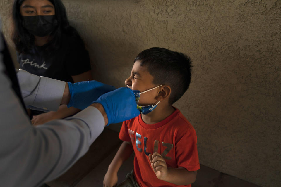 Shahir Sanchez, 5, grimaces as Dr. Neal Schwartz collects a nasal swab sample for COVID-19 testing at Families Together of Orange County Thursday, Aug. 26, 2021, in Tustin, Calif. (AP Photo/Jae C. Hong)