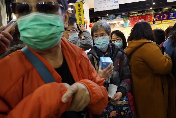 A woman holds a box of face mask as people queue up waiting to purchase face masks outside a shop in Hong Kong, Wednesday, Jan. 29, 2020. A viral outbreak that began in China has infected more than 6,000 people in the mainland and more than a dozen other countries. (AP Photo/Vincent Yu)