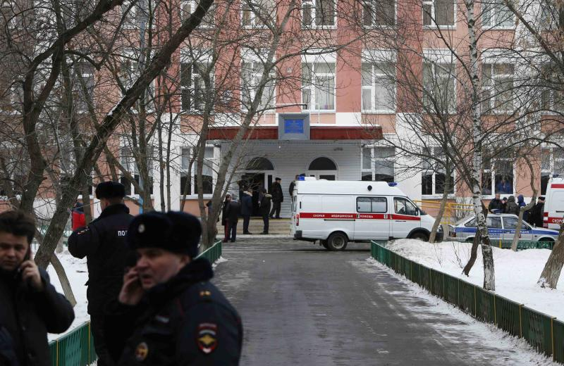 Interior Ministry members and other authorities gather outside a high school on the outskirts of Moscow