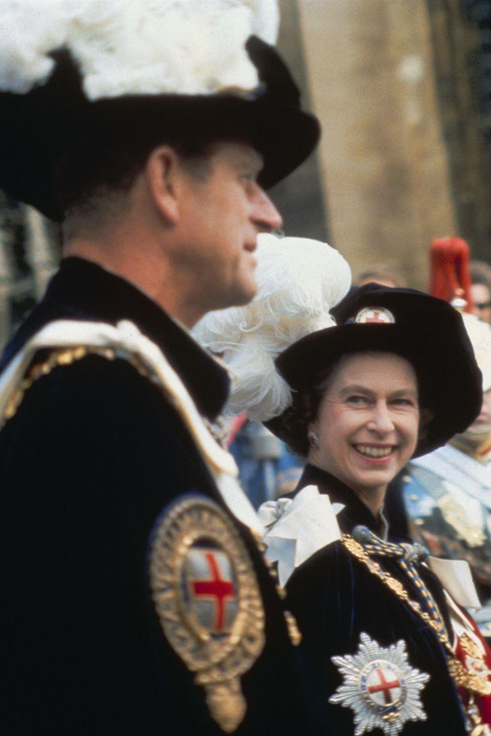 <p>Queen Elizabeth smiles at her husband, Prince Philip, during a garter ceremony at Windsor Castle in 1957. </p>