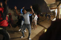 People are seen celebrating the new year on the streets in Mbare, Harare, Friday, Jan 1, 2021. Despite a government ban on music concerts and public gatherings due to a surge in COVID-19 infections and the new and more contagious variants of the disease, thousands of people gathered in one of the country's poorest neighborhoods to celebrate the new year.(AP Photo/Tsvangirayi Mukwazhi)