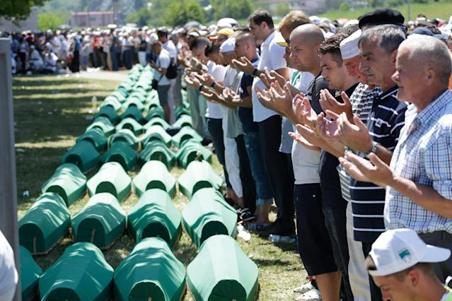 <p>Bosnian Muslim people pray in front of coffins during a funeral ceremony for dozens of newly identified victims of the 1995 massacre, at the memorial centre of Potocari near Srebrenica, 150 kms north east of Sarajevo, Bosnia, Tuesday, July 11, 2017. (Photo: Amel Emric/AP) </p>