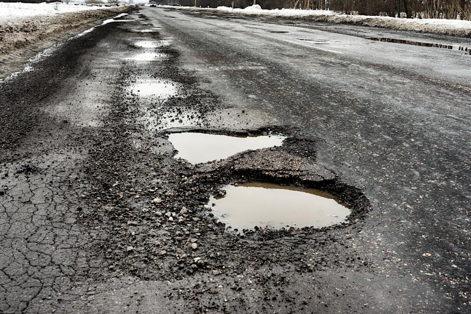 old highway with holes and snow. Landscape road in the potholes in cloudy winter weather. The concept of the absence of timely repair of the highway.