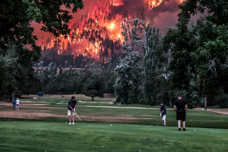 The Eagle Creek wildfire burns as golfers play at the Beacon Rock Golf Course in North Bonneville, Washington, on September 4, 2017.