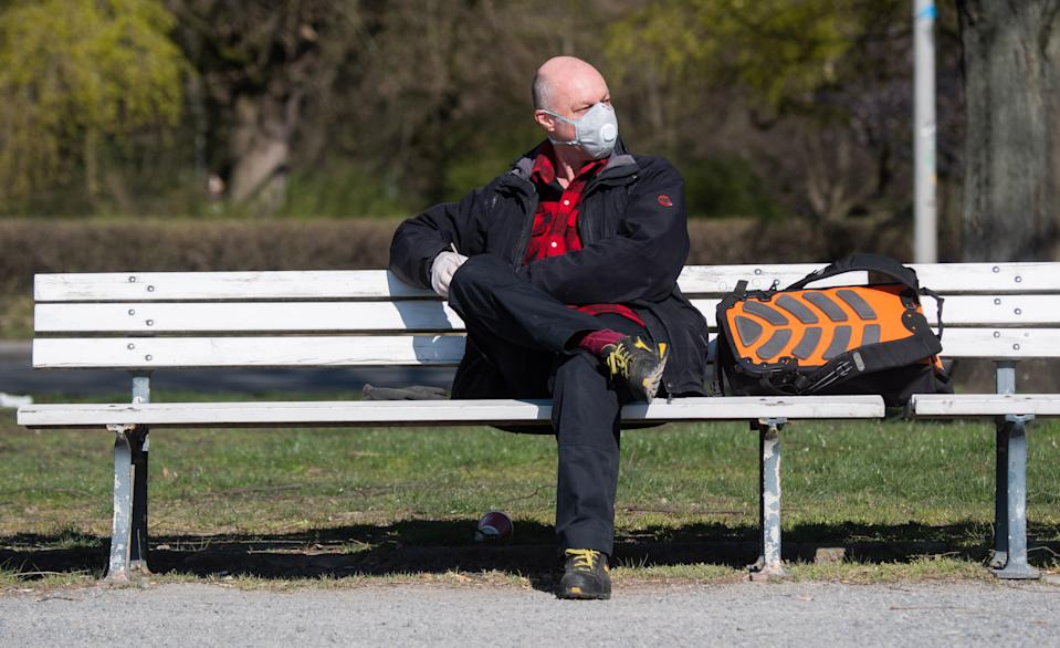 25 March 2020, Lower Saxony, Hanover: Marco Lodolo is sitting at the Maschsee with a breathing mask. Photo: Julian Stratenschulte/dpa (Photo by Julian Stratenschulte/picture alliance via Getty Images)
