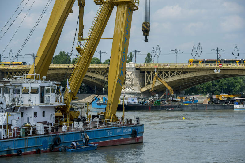 Preparations are made to lift the sunk shipwreck at Margaret Bridge, the scene of the deadly boat accident in Budapest, Hungary, Monday, June 10, 2019. A sightseeing boat carrying 33 South Korean tourists was crashed by a large river cruise ship and sank in the River Danube on May 29, 2019. (Tamas Soki/MTI via AP)