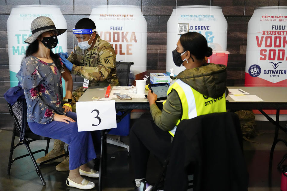 FILE - In this March 25, 2021, file photo, Jing Wang, left, receives a vaccine at Mercedes-Benz Stadium in Atlanta. A new poll from The Associated Press-NORC Center for Public Affairs Research shows that the percentage of Americans resisting getting inoculated has shrunk in the past few months. But it's still not enough to pull America out of the pandemic, and reach herd immunity. (AP Photo/Brynn Anderson, File)
