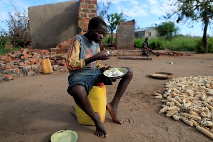 "Bernado Jofresse, 14, eats rice for breakfast as he sits beside his family's damaged house in the aftermath of Cyclone Idai, in the village of Cheia, which means ""Flood"" in Portuguese, near Beira, Mozambique April 3, 2019. (Photo: Zohra Bensemra/Reuters)"