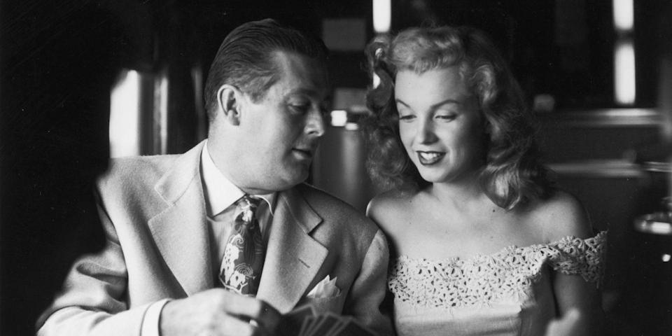 """<p>Monroe rides a train and plays cards with Don Defore from New York City to Warrenburg, New York. She was in New York City to promote her new film <em>Love Happy</em> and was traveling with Defore to present Photoplay Magazine's 'Dream Home' contest winner Virginia McAllister a key to her new house<span class=""""redactor-invisible-space"""">. </span></p>"""
