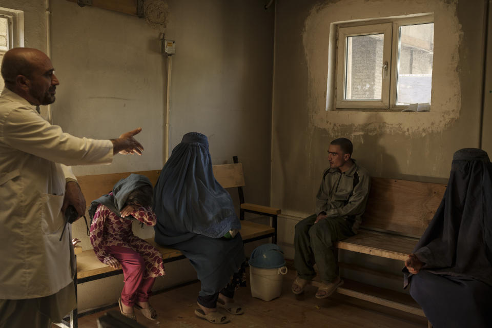 Dr. Wahedullah Koshan, left, gestures as he talks to Sitara, center, after she reunited with her 21-year-old son who was taken to the Avicenna Medical Hospital for Drug Treatment during a Taliban raid in Kabul, Afghanistan, Monday, Oct. 4, 2021.
