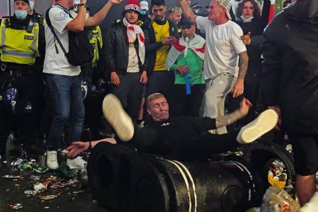 A football fan tumbles over a rubbish bin as they party in Piccadilly Circus, London