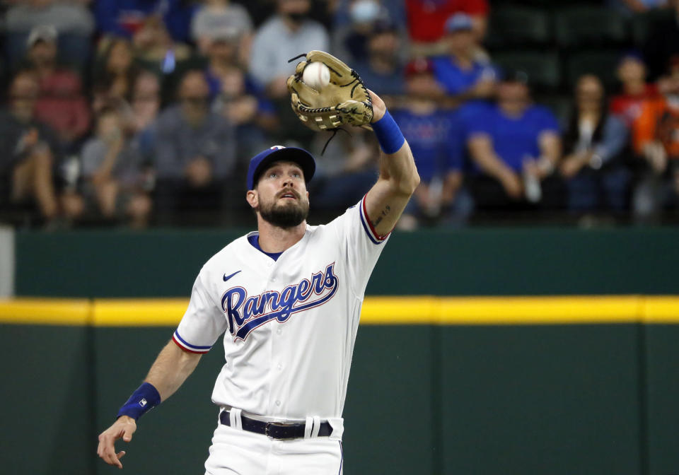 Texas Rangers left fielder David Dahl makes the catch of a fly ball during the first inning of a baseball game in Arlington, Texas, Saturday, April 17, 2021. (AP Photo/Ray Carlin)