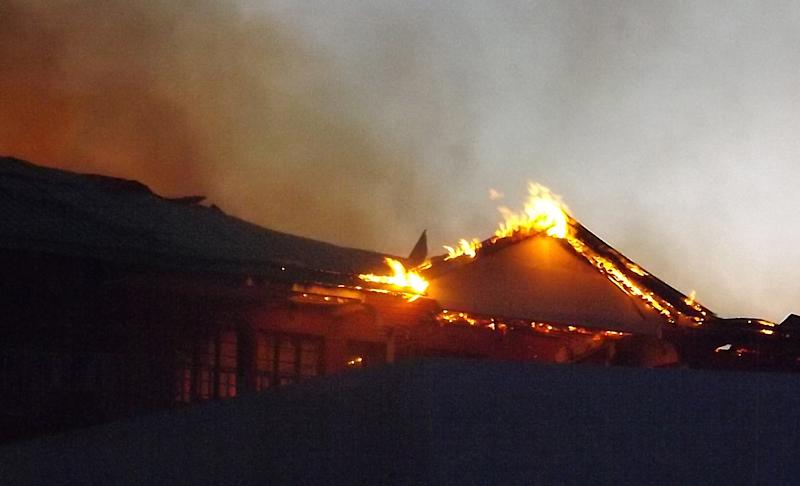 The Garissa Halgan Quran House Resort Hotel is engulfed in flames, in Garissa, Northern Kenya, Monday, Nov. 19,  2012, after Kenya Defense Forces swept into Garissa, Kenya,  beating people and burning property as they went Monday, Nov. 19, 2012.  It is reported that the KDF forces swept through Garissa, beating people as they moved through the town near the Somali border, and most people living there are Somalis. (AP Photo/Daud Yusuf)