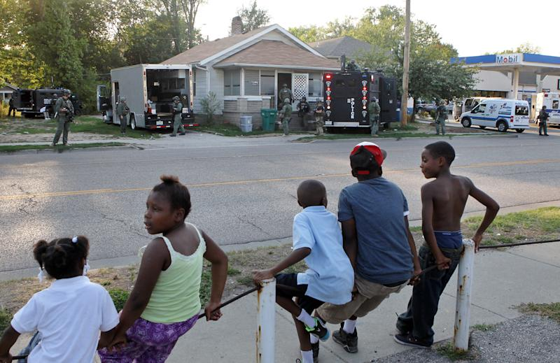 Neighborhood children watch as members of the Madison County tactical response team secure a house Thursday evening, Aug. 23, 2012 in Washington Park, Ill. A teenage girl reported missing more than two years ago escaped from the Southwestern Illinois home where she said she was held captive and repeatedly sexually assaulted, police said Thursday. Police in Washington Park, a village next to East St. Louis, said the girl reported that she was raped by her captor, got pregnant and had a baby. (AP Photo/St. Louis Post-Dispatch, J.B. Forbes) EDWARDSVILLE INTELLIGENCER OUT; THE ALTON TELEGRAPH OUT