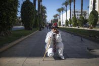 Belhussein Abdelsalam, a Charlie Chaplin impersonator performs on a main avenue in Rabat, Morocco, Saturday, March 13, 2021. When 58-year-old Moroccan Belhussein Abdelsalam was arrested and lost his job three decades ago, he saw Charlie Chaplin on television and in that moment decided upon a new career: impersonating the British actor and silent movie maker remembered for his Little Tramp character. (AP Photo/Mosa'ab Elshamy)
