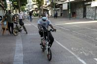 An asylum seeker from Sudan rides his bicycle on a street in southern Tel Aviv, where thousands of Sudanese live