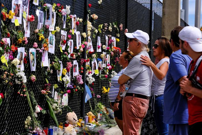 People mourn at the memorial site created by neighbors in front of the partially collapsed building where the rescue personnel continue their search for victims in Surfside, Fla., on June 26, 2021. (Maria Alejandra Cardona / Reuters)