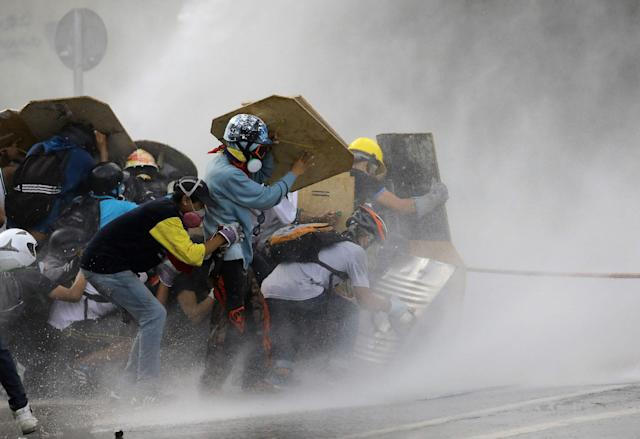 <p>Demonstrators clash with riot security forces while rallying against President Nicolas Maduro in Caracas, Venezuela, May 27, 2017. (Carlos Barria/Reuters) </p>