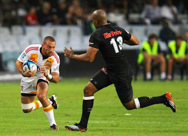 New Zealand Waikato Chiefs' Aaron Cruden (L) is charged by Sharks of Durban's JP Pietersen during the Super 15 rugby union match Sharks of Durban vs Waikato Chiefs of New Zealand at the Mr Price Kings Park Rugby Stadium on April 21, 2012. AFP PHOTO/ STR (Photo credit should read -/AFP/Getty Images)