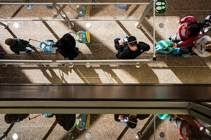 Travelers wait in line for security screening at Seattle-Tacoma International Airport