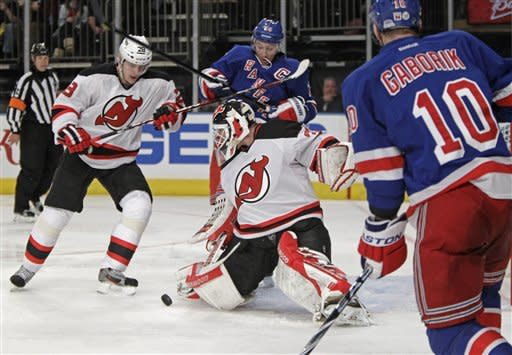 New York Rangers right wing Marian Gaborik (10) watches as New Jersey Devils goalie Martin Brodeur (30) blocks a shot with his knee pad with Devils defenseman Anton Volchenkov (28) and Rangers right wing Ryan Callahan (24) watch in the second period of their NHL hockey game at Madison Square Garden in New York, Monday, Feb. 27, 2012. (AP Photo/Kathy Willens)