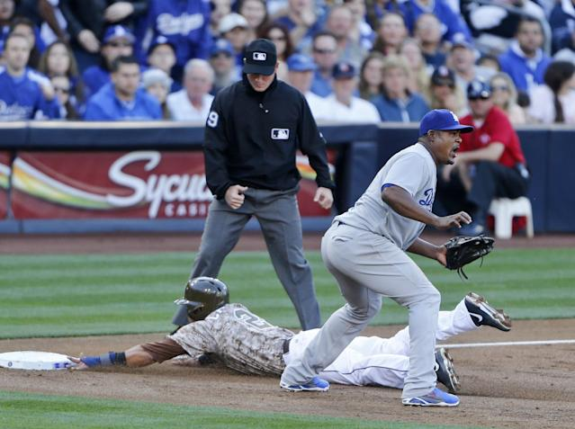 San Diego Padres' Everth Cabrera slides into third safely as Los Angeles Dodgers third baseman Juan Uribe awaits a late throw in the first inning of the opening game of Major League baseball in the United States Sunday, March 30, 2014, in San Diego. (AP Photo/Lenny Ignelzi)