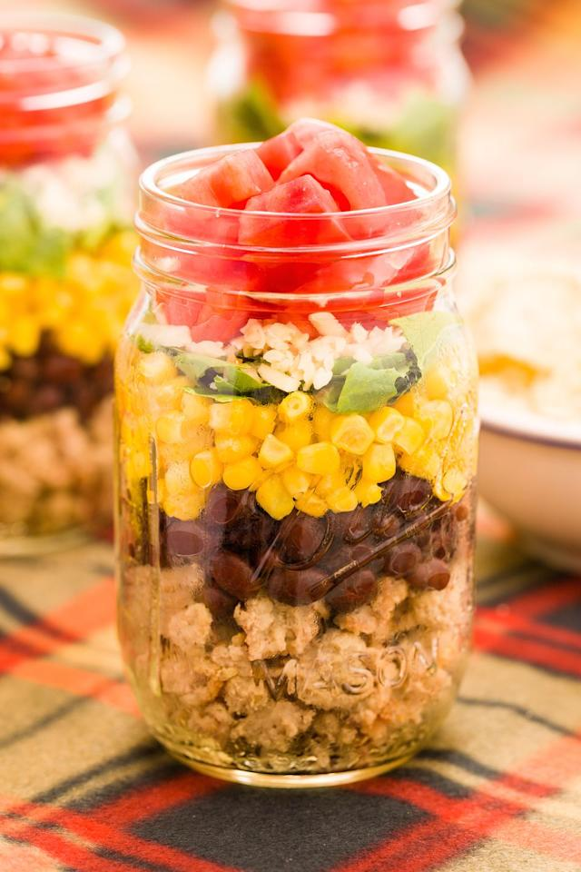 "<p>Layers of minced turkey, black beans, corn, spring onions, cheese, and tomatoes is the heartiest thing you can tote along to your tailgate.</p><p>Get the <a href=""https://www.delish.com/uk/cooking/recipes/a29891198/taco-salad-in-a-jar-recipe/"" target=""_blank"">Taco Salad Jar</a> recipe. </p>"