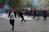 Demonstrators run from tear gas during a protest against Chile's state economic model in Santiago