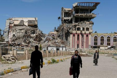 People walk in front of the remains of the University of Mosul, which was burned and destroyed during a battle with Islamic State militants, in Mosul, Iraq, April 10, 2017. REUTERS/Marko Djurica