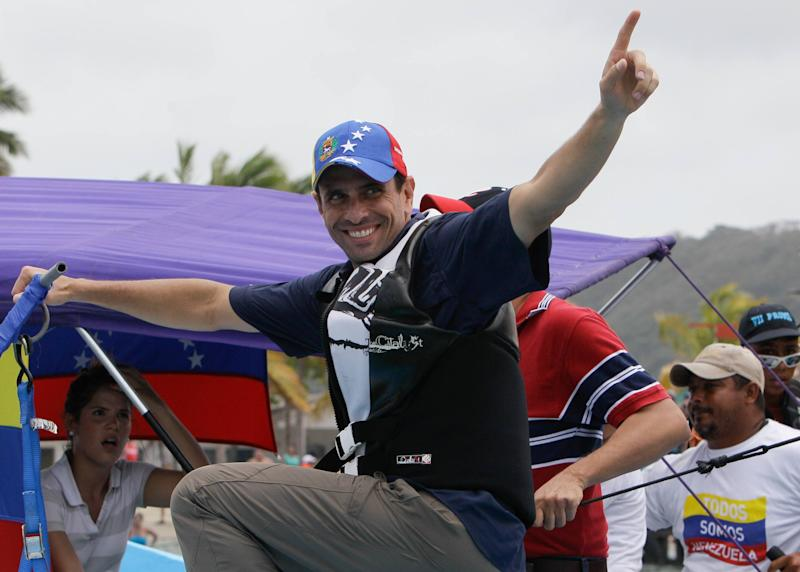 Opposition presidential candidate Henrique Capriles greets vacationing residents during a rally at Morrocoy Keys a resort near Chichiriviche, Venezuela, on Good Friday, March 29, 2013. Holy Week in Venezuela is a time when millions traditionally take a welcome pause from work and politics to go on vacation. Yet that hasn't stopped Venezuela's time-pressed presidential candidates from sprinting through the holidays toward an April 14 election to replace the late Hugo Chavez, as they try to define both themselves and each other within weeks. Capriles will run against Chavez's chosen successor, acting President Nicolas Maduro.(AP Photo/Fernando Llano)