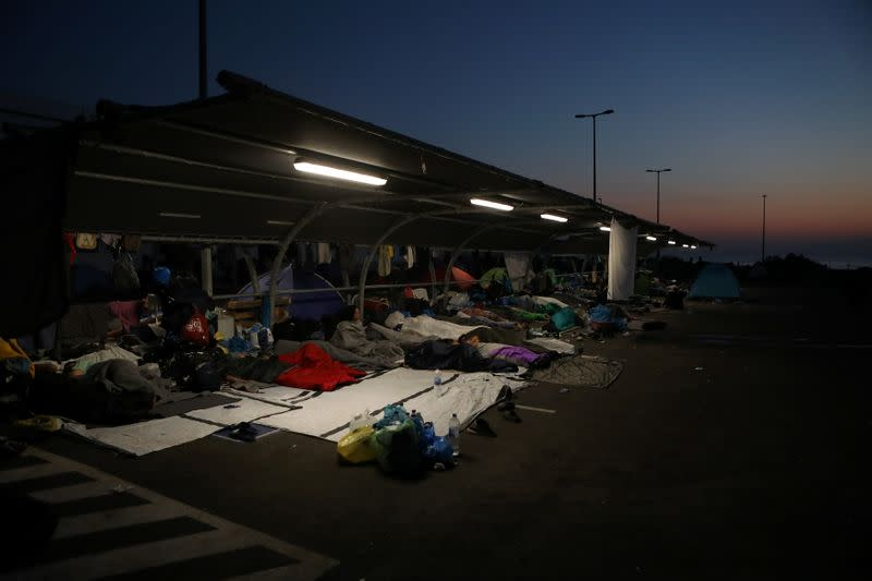 Refugees and migrants from the destroyed Moria camp find shelter at the parking space of a supermarket, near a new temporary camp on the island of Lesbos