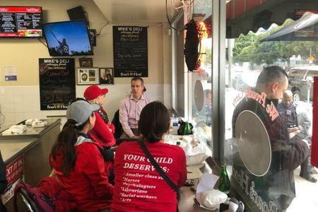 Los Angeles Mayor Eric Garcetti sits at a deli counter and talks with striking teachers in downtown Los Angeles, California, U.S., January 15, 2019. REUTERS/Alex Dobuzinskis