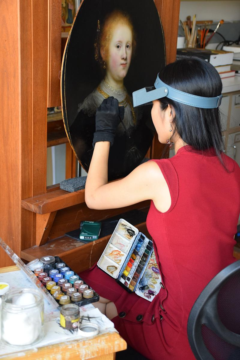 Conservator Shan Kuang, working on the painting.