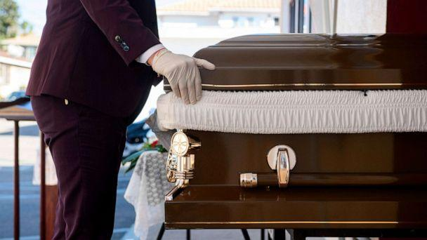 PHOTO: Funeral director Steven Correa wears gloves as he moves the casket of Gilberto Arreguin Camacho, 58, in preparation for burial following his death due to Covid-19 at Continental Funeral Home on  Dec. 31, 2020, in East Los Angeles, Calif. (Patrick T. Fallon/AFP via Getty Images)