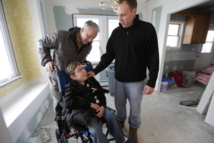 Donald Denihan, left, chats with firefighter Chris Troy, right, and Chris's son Connor, 12, who suffers from a life-threatening neuromuscular disease, at the family's partially renovated home in Long Beach, N.Y., Wednesday, Dec. 12, 2012. Denihan, who was looking to help a family after the Superstorm Sandy, is paying to renovate the Troy's house. (AP Photo/Kathy Willens)