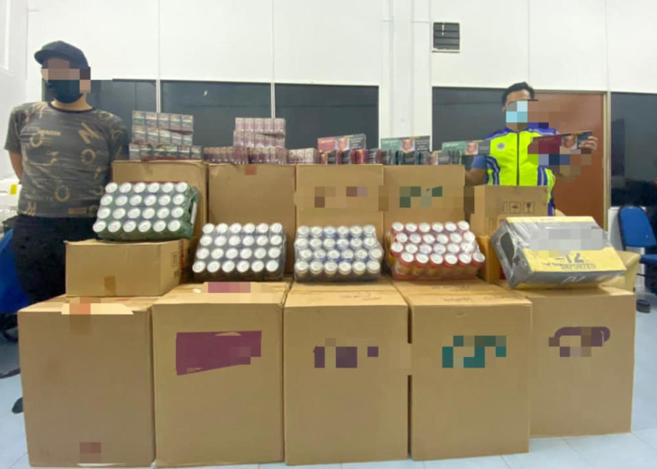 Region Two Marine Police Force personnel with the seized contraband cigarettes and alcohol at a premises in Taman Kempas, Johor Baru July 30, 2021. — Picture courtesy of the Region Two Marine Police Force