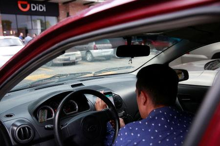 A new DIDI driver set up his mobile phone inside a car outside the new drivers center of the Chinese ride-hailing firm in Toluca, Mexico, April 23, 2018. REUTERS/Carlos Jasso