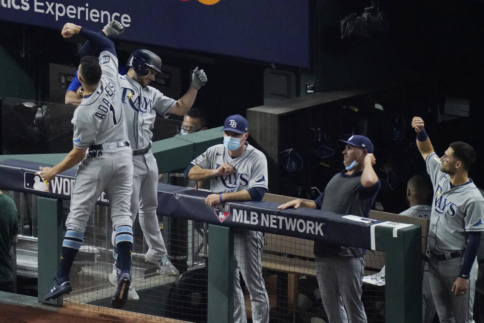 Tampa Bay Rays' Brandon Lowe celebrates his home run with Willy Adames against the Los Angeles Dodgers during the first inning in Game 2 of the baseball World Series Wednesday, Oct. 21, 2020, in Arlington, Texas. (AP Photo/Sue Ogrocki)