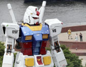 An 18-meter (60-foot) tall Gundam stands over visitors to a Tokyo waterfront park Saturday, July 18, 2009. The full-size model of Japan's popular robot animation character was built, marking the 30th anniversary of the start of broadcasting of the animation. Gundam is a giant robot that has a roll in the era of space wars. (AP Photo/Koji Sasahara)