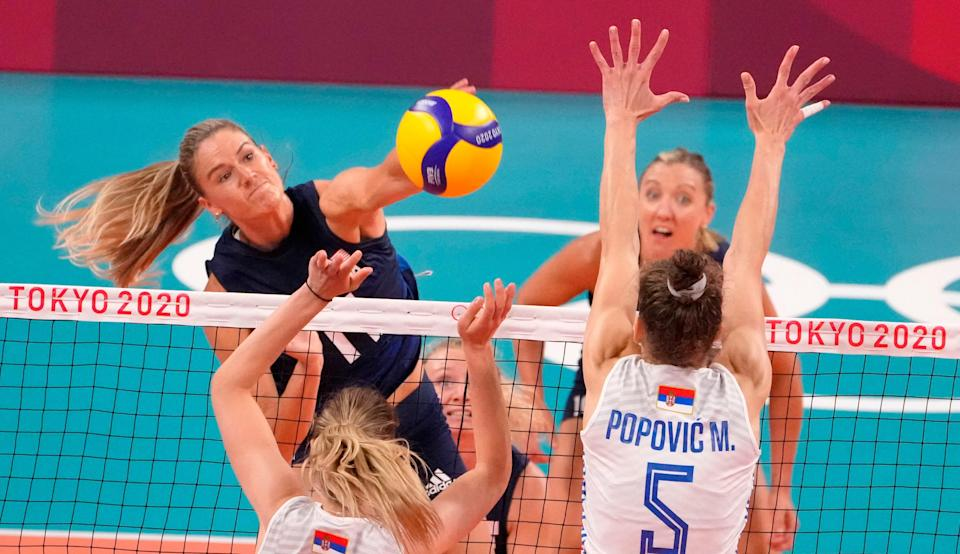 USA player Andrea Drews (11) hits the ball as Serbia player Mina Popovic (5) defends.