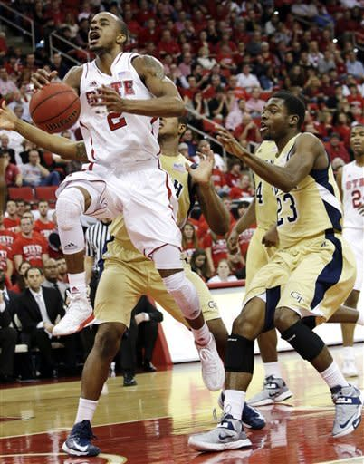 North Carolina State's Lorenzo Brown drives to the basket past Georgia Tech's Marcus Georges-Hunt and Brandon Reed (23) during the first half of an NCAA college basketball game in Raleigh, N.C., Wednesday, Jan. 9, 2013. (AP Photo/Gerry Broome)